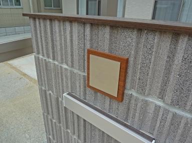 玄関ドアの木調とマッチした表札。
